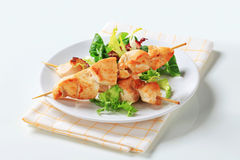 Chicken skewers and salad greens Royalty Free Stock Photo