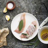 Chicken small breasts with sage leaves, floral honey, salt, olive oil, garlic, with thin strips of bacon before baking Royalty Free Stock Images