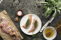 Chicken small breasts with sage leaves, floral honey, salt, olive oil, garlic, with thin strips of bacon before baking Royalty Free Stock Photo