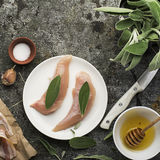 Chicken small breasts with sage leaves, floral honey, salt, olive oil, garlic, with thin strips of bacon before baking Stock Images