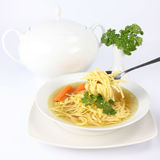 Chicken soup. With macaroni and carrots decorated with parsley on a plate, some of it on a spoon , with soup tureen and parsley in the background stock photos