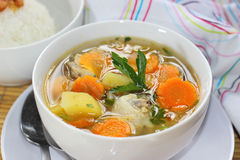 Chicken Soup. A bowl of Chicken Soup served with slices of potato and carrots Stock Photos