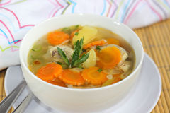 Chicken Soup. A bowl of Chicken Soup served with slices of potato and carrots Royalty Free Stock Images