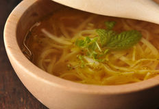 Chicken soup - broth. In wooden bowl Stock Images