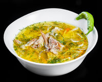 Chicken soup - broth with noodles, herbs and vegetables in bowl, isolated on black background, healthy food. Top view Stock Images