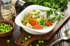 Chicken soup with green peas Stock Photo