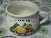 Chicken Soup Mug by Kambas. A soup mug with chicken soup written in text including a picture of a chicken with vegetables on a tablecloth Stock Images