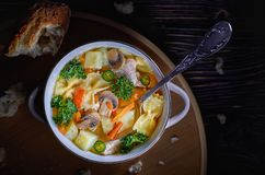 Chicken soup with mushrooms and herbs in a low key stock images