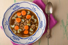 Chicken soup on old vintage table with carrots and selery on top Stock Photography