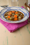 Chicken soup on old vintage table with carrots and selery on top Royalty Free Stock Photo