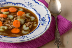 Chicken soup on old vintage table with carrots and selery on top Royalty Free Stock Photos