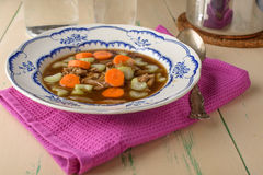 Chicken soup on old vintage table with carrots and selery on top Stock Photos