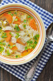Chicken soup with pasta. Farfalle in the bowl on wooden table Stock Photo