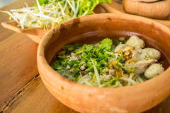 Chicken soup with rice, egg and noodles in brown clay pot on a w Royalty Free Stock Photos