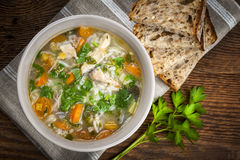 Chicken soup with rice and vegetables. Chicken rice soup with vegetables in bowl and bread from above Royalty Free Stock Image