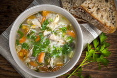Chicken soup with rice and vegetables. Chicken rice soup with vegetables in bowl and bread from above Royalty Free Stock Photos