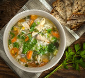Chicken soup with rice and vegetables. Chicken rice soup with vegetables in bowl and bread from above closeup Stock Photos