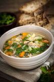 Chicken soup with rice and vegetables. Chicken rice soup with vegetables in bowl and bread on rustic table Stock Photo