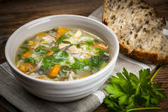 Chicken soup with rice and vegetables. Chicken rice soup with vegetables in bowl and bread on rustic table Royalty Free Stock Photo