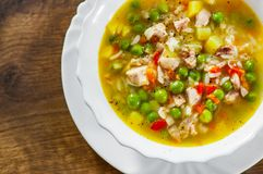Chicken soup with rice and vegetables in bowl on wooden table royalty free stock images