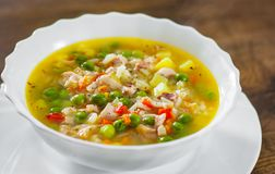 Chicken soup with rice and vegetables in bowl on wooden table royalty free stock photography