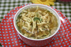 Chicken Soup. A chicken soup with some slices of a pancake royalty free stock images