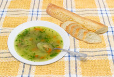 Chicken soup in white dish and baguette on checkered tablecloth Stock Images