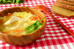 Chicken soup in a wooden plate. Chicken with noodles soup in a wooden bowl. on a red tablecloth into the cell.dark bread Royalty Free Stock Images