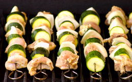 Chicken Souvlaki. Five stainless steel skewers with chicken meat, onions and zucchini on the grill Royalty Free Stock Images