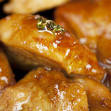 Chicken in soy sauce. Large pieces of chicken fry in soy sauce in a frying pan, close-up photo Stock Image