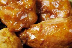 Chicken in soy sauce. Large pieces of chicken fry in soy sauce in a frying pan, close-up photo Stock Photo