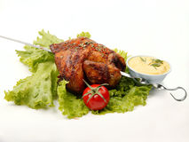 Chicken on spit. Grilled chicken on spit with herbs and vegetables Royalty Free Stock Photography