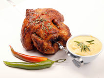 Chicken on spit. Grilled chicken on spit with herbs and vegetables Royalty Free Stock Photos