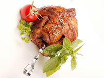 Chicken on spit. Grilled chicken on spit with herbs and vegetables Stock Photo