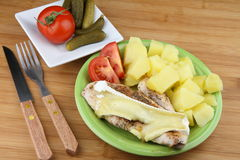 Chicken steak. From breast with spice and cheese on plate with potatoes and sliced tomato. Pickled cucumbers and tomato on other plate Royalty Free Stock Photo