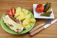 Chicken steak. From breast with spice and cheese on plate with potatoes and sliced tomato. Pickled cucumbers and tomato on other plate Stock Photo