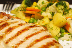Chicken steak. Closeup of a chicken grilled steak with vegetables and potatoes royalty free stock photo