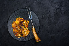 Chicken steak on slate board. Chicken steak, fork and knife on slate board. Dark stone background. Copy space stock image
