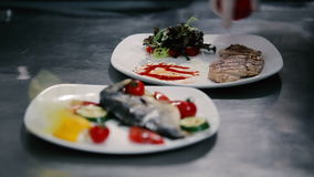 Chicken steak and lettuce watered oil. Man puts the pieces of sliced steak on a white plate. Two dishes are on the table cuisine. Chef working in rubber gloves stock footage
