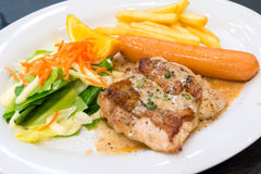 Chicken steak with sausage and salade  on white dish Stock Image