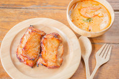 Chicken steak and spicy soup on wooden table Royalty Free Stock Images