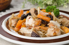 Chicken stew with carrots and prunes on a plate, closeup, select Stock Image