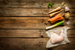 Chicken stock bouillon, soup ingredients on wood Royalty Free Stock Images