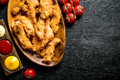 Chicken strips with cherry tomatoes and various sauces royalty free stock photo