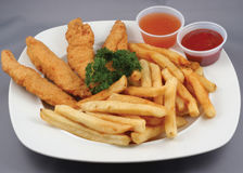 Chicken strips and fries combo. Plated meal of chicken strips and fries with ketchup and dipping sauce Stock Image