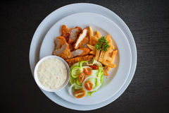 Chicken strips and fries combo on black wood Royalty Free Stock Photography