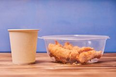 Chicken strips in a plastic container with a paper Cup on a wooden table.  stock photography