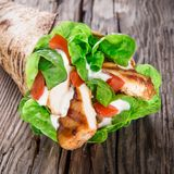 Chicken strips in Tortilla wrap. On wooden background Royalty Free Stock Photography