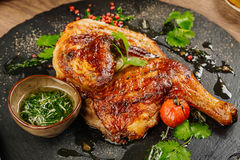 Chicken Tabaka with sauce on stone plate. Stock Photography