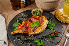Chicken Tabaka with sauce on stone plate. Stock Image